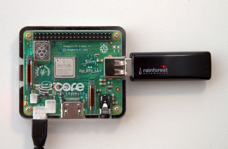 Rasperry Pi 3 model A+ in a Core Electronics Slim Case and a Rainforest RAVEn plugged in to the USB port